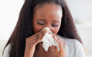 Female using tissue to blow her nose