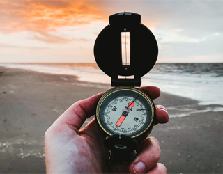 A hand viewing a compass