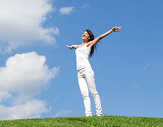 Woman enjoying the sunshine with her arms outstretched