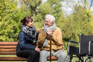 Elderly man with female caretaker on park bench