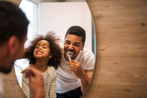 Father and daughter brusing teeth and smiling in front of mirror