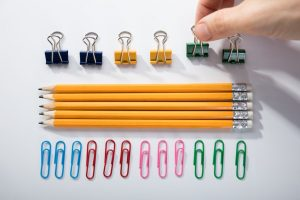 Person's hand meticulously arranging pencils and clips