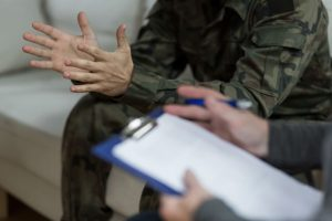 Soldier sitting on sofa across from counselor