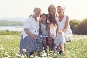 Sonriendo hija, madre y abuela sentada afuera
