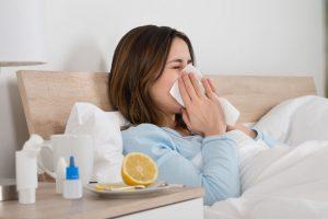 mujer en la cama sonarse la nariz