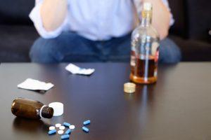 hombre con pastillas y alcohol